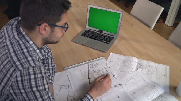 Cover Image for Architect Man Correct Design On Blueprint In The Office.