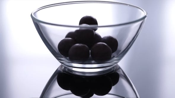 Thumbnail for Round Chocolate Candies Falling Down In a Glass Bowl
