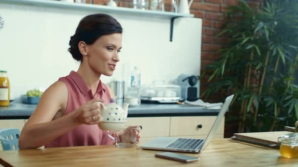 Thumbnail for Woman Pouring Tea Into Cup During Video Call. Girl Using Laptop for Video Chat.