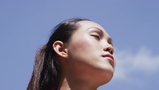 Thumbnail for Young woman taking a break from running with sun in her face
