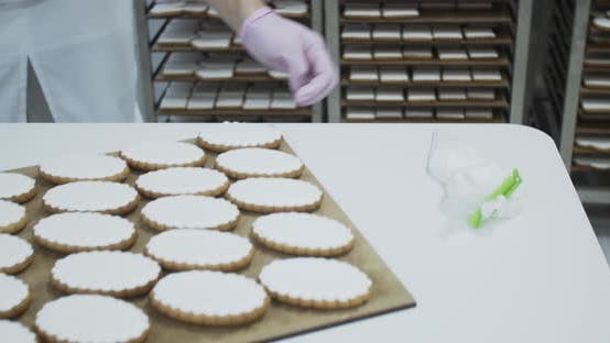 Bakery Worker is Putting Gingerbread Cookies on the Shelf After Putting Icing