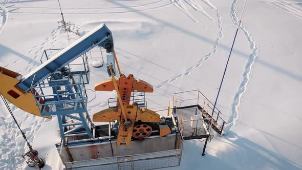 Thumbnail for Aerial View of Pumpjack on Oil Well in Snowy Field in Winter Day