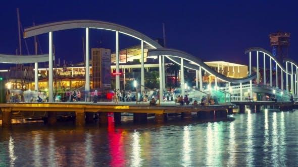 Thumbnail for Illuminated Bridge In Port Vell Marina At Night. Light Reflections On Water