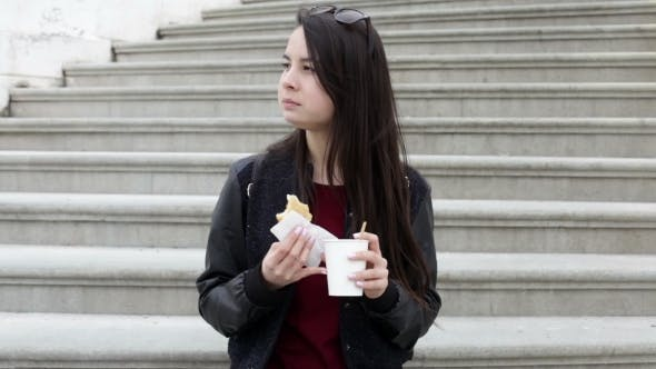 Thumbnail for Young Asian Woman Eating Sandwich and Drinking Coffee Outdoors
