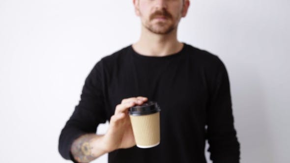 Thumbnail for Handsome Bearded Unfocused Guy Shows Paper Cup On Camera