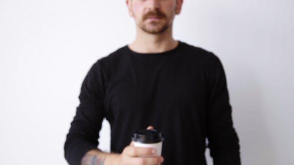 Handsome bärtige unfokussierte Kerl zeigt Papier Tasse auf Kamera