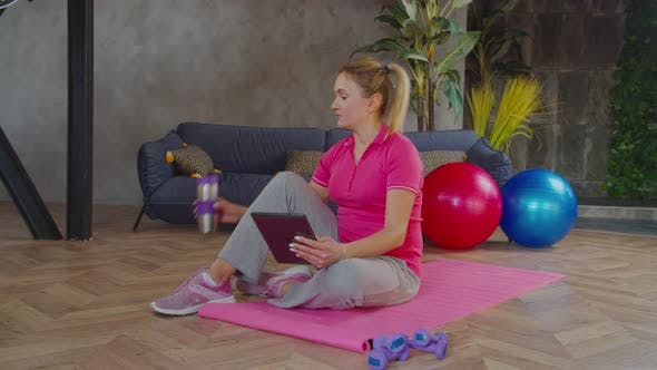Sporty Woman Video Conferencing with Fitness Trainer