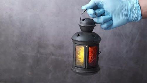 Hand in Gloves Holding Lantern Light Against Black Background