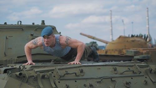 Der Soldat hat auf den Panzer geschoben