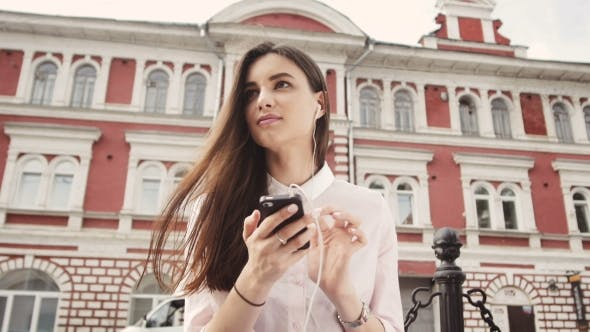 Thumbnail for Smiling Urban Girl Uses Smart Phone With Smile On Her Face
