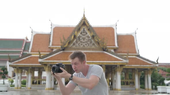 Thumbnail for Young Happy Tourist Man Photographing Around the Buddhist Temple in Bangkok