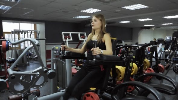 Thumbnail for Woman Is Engaged In Gym On Exercise Equipment On Raising Legs.