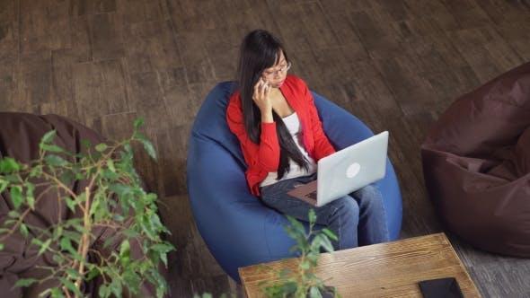 Thumbnail for asiatische frau arbeiten in loft sitzen auf sitzsack stühle