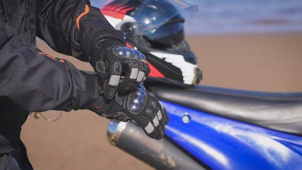 Thumbnail for Biker In The Street Next To His Bike, Puts On Gloves.