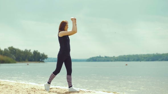 Beautiful Red-haired Girl Doing Exercises on the River.