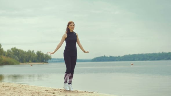 Cover Image for Beautiful Red-haired Girl Doing Exercises On The River.