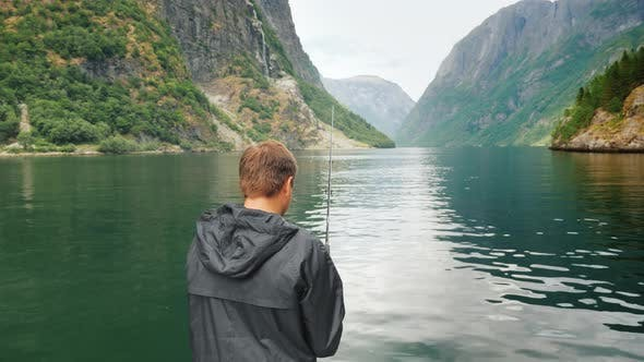 Cover Image for A Man Is Fishing Against the Backdrop of the Picturesque Norwegian Fjords