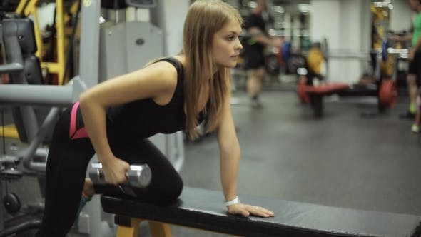Thumbnail for Woman In Gym Lifting Dumbbell At Bench.