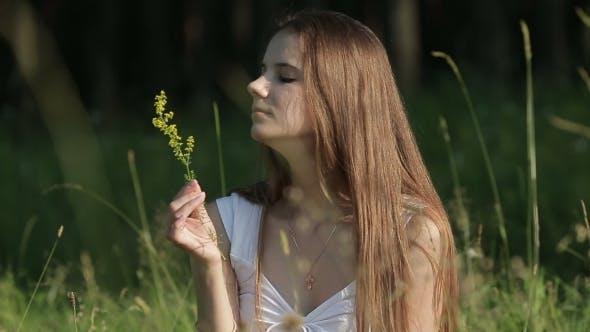 Genuine Woman In Meadow Sniffing Flower