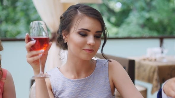 Thumbnail for Girl with friends drinking wine in a restaurant