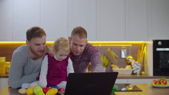 Same-sex Couple and Baby Watching Cartoon Online