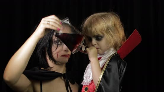 Thumbnail for Frau und Kind Dracula. Halloween Vampir Make-up Kind mit Blut auf Ihr Gesicht