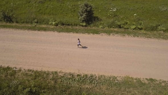 Thumbnail for Girl Runs On The Road In a field.Aerial View.