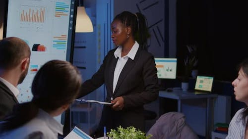 Workaholic African American Leader Standing in Front of Presentation Monitor Explaining Marketing
