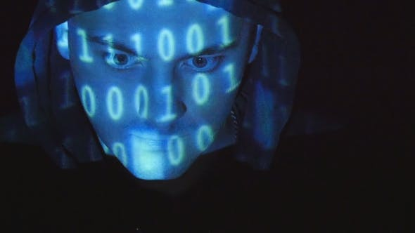 Thumbnail for Hooded Hacker Working On a Computer, Binary Code Projecting On His Face. Source Code Projected Over