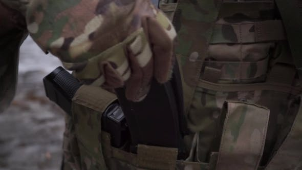Soldier Puts Assault Rifle Ammo Into Pockets Of His Ammo Vest