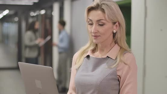 Thumbnail for Close-up of Blond Adult Caucasian Woman Standing with Laptop in Open Space Office, Looking at Camera