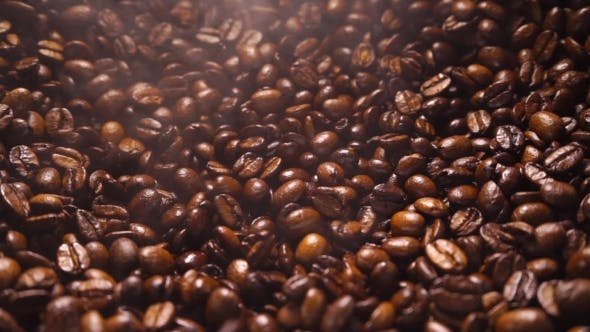 Thumbnail for Coffee Beans Falling Down on a a Pile of Smoking Roasted Coffee Beans