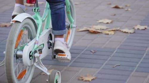 Little Girl fährt Fahrrad auf Autumn City Boulevard, Rückansicht