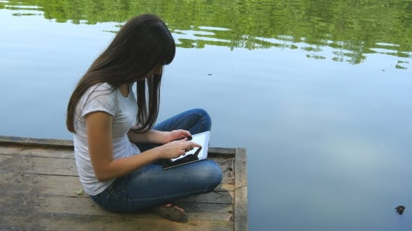 Thumbnail for Girl Using Tablet Pc And Relaxes By The Lake Sitting On The Edge Of a Wooden Jetty Near The Water