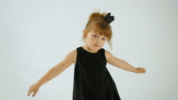 Thumbnail for Cute Little Girl In Black Dress Dancing And Having Fun, Isolated On White
