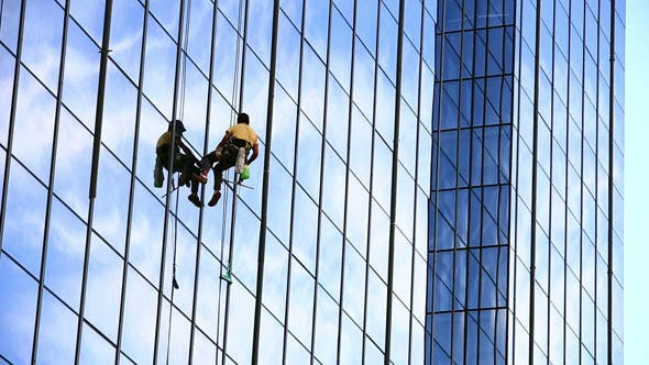 Cover Image for Man Cleaning Windows of Office Building