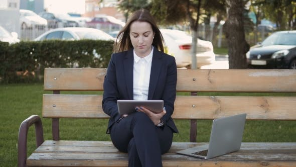 Thumbnail for Young Beautiful Business Woman Using Tablet PC Sitting On Bench Outdoors