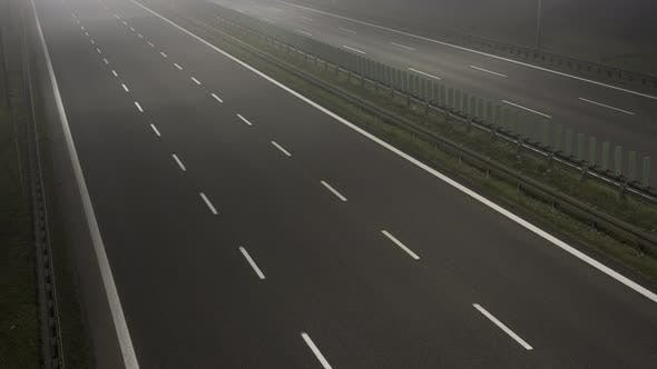 Cars Driving Fast on a Motorway or Highway with Fog or Mist