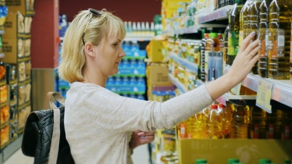 Thumbnail for Young Woman Looking At a Bottle Of Olive Or Other Oil In The Supermarket