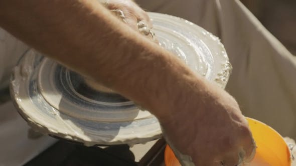Thumbnail for Dirty Pottery Wheel Is Spinning Around Under Hands Of Craftsman
