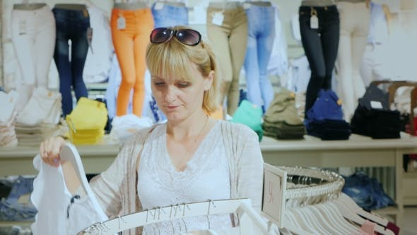 Thumbnail for Young Woman Chooses Clothes In a Shop. It Should Be Against The Background Stands With Clothes