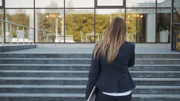 Thumbnail for Young Business Woman Walking Up On Stairs And Making a Phone Call, Outdoors