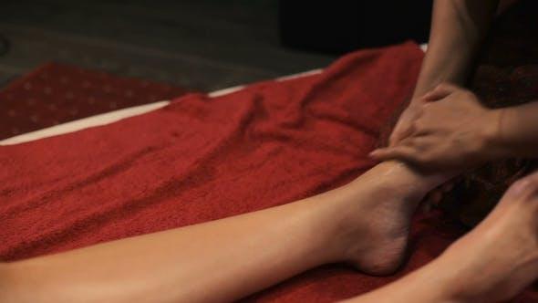 Thumbnail for Masseur Rubs Oil Left Foot Oil.