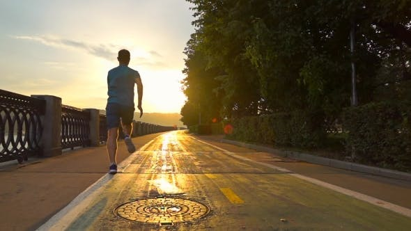 Thumbnail for Man In Blue Uniform Running On Sunset Embankment Along Bicycle Road