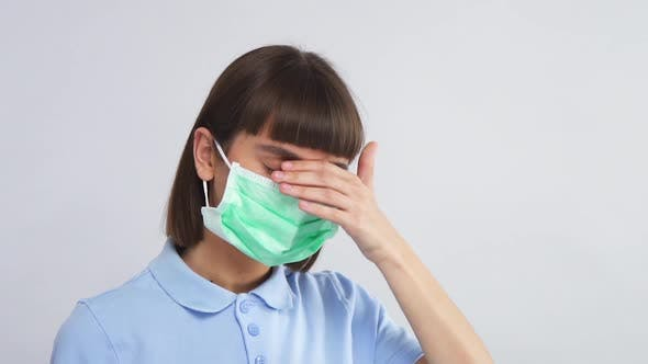 Thumbnail for Sick Person in Protective Respiratory Mask and Blue Shirt Touching Forehead with Arm To Check Body