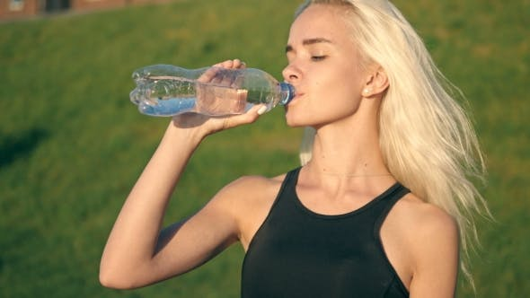 Thumbnail for Sporty Woman Drinking Water Outdoor On Sunny Day On Sunset