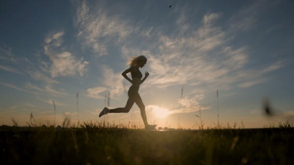 Thumbnail for Silhouette Of a Sexy Fit Woman Girl Running At Sunset. Training, Jogging, Healthy Lifestyle.