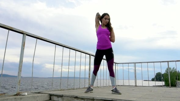 Thumbnail for Fitness Girl On The Embankment Of The River. Perform Stretching. .