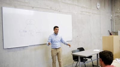 Teacher At White Board With Scheme On Lecture