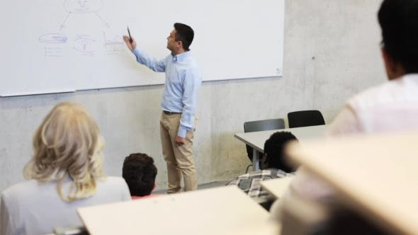 Teacher At White Board And Students On Lecture